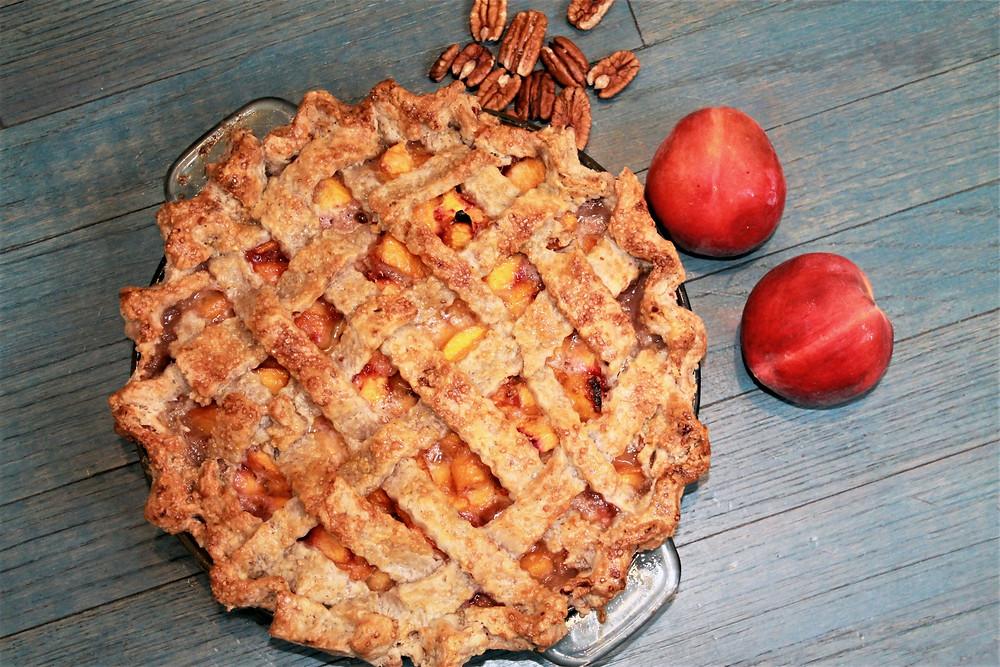 Homemade lattice peach pie next to peaches and pecans