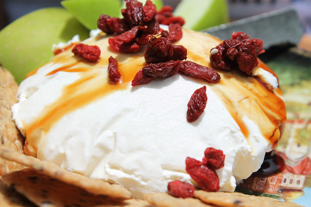 kefir cheese topped with honey, goji berries, and served with green apple and crackers