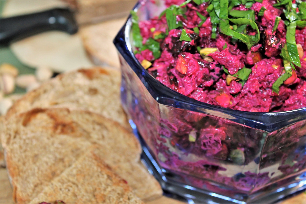 Beet salad in a clear glass bowl topped with greens with slices of bread on the side