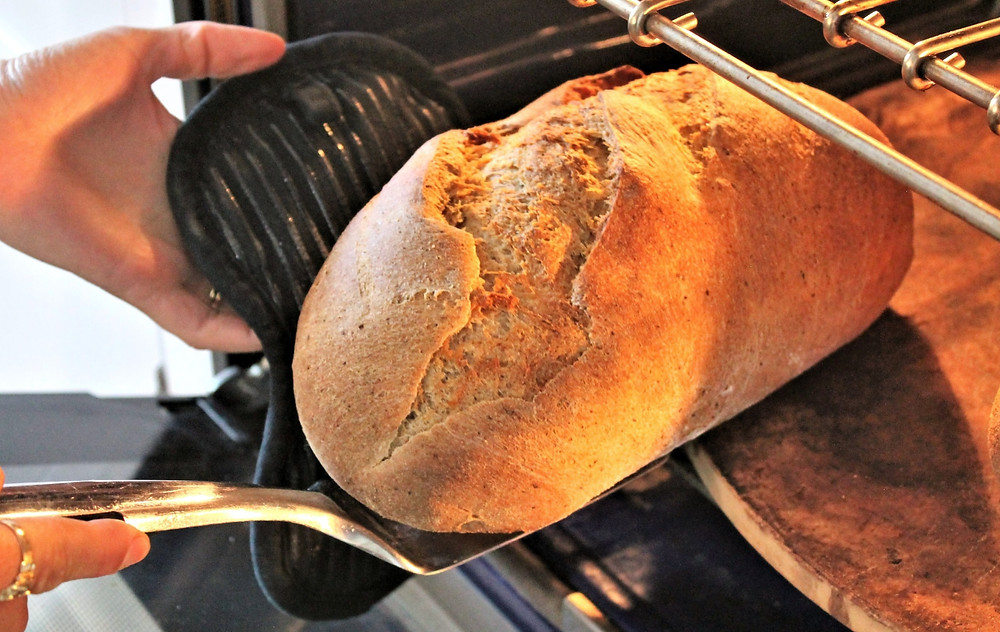 taking bread out of the oven