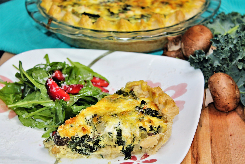 quiche whole baked and slice on a plate with side salad
