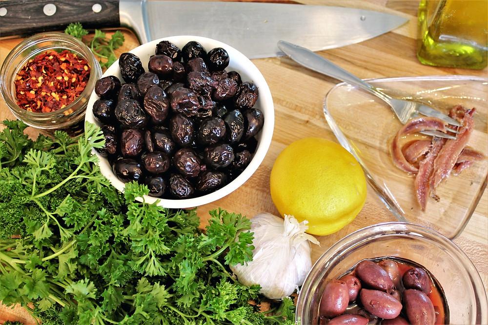 black olives, anchovies, red pepper flax, lemon, garlic, parsley, and Kalamata olives