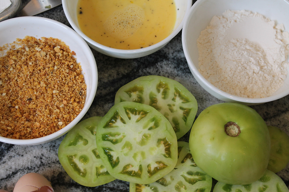 sliced green tomatoes, three bowls with bread crumbs, egg wash, flour