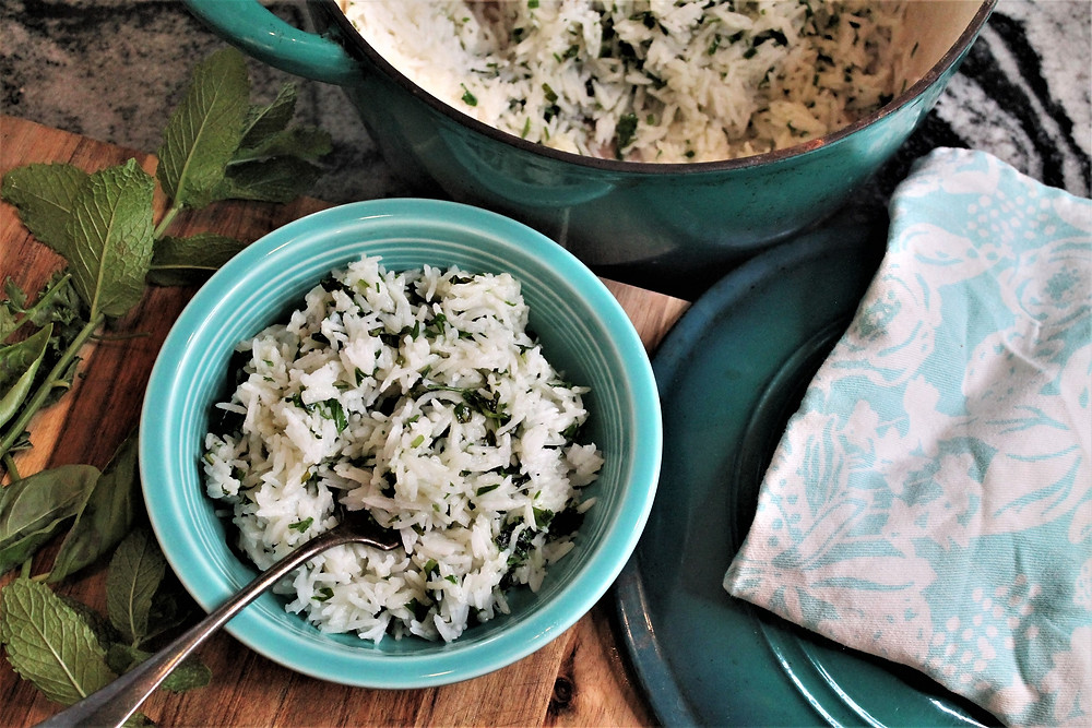 bowl of herb and butter rice, big green pot, lid and kitchen towel, herbs