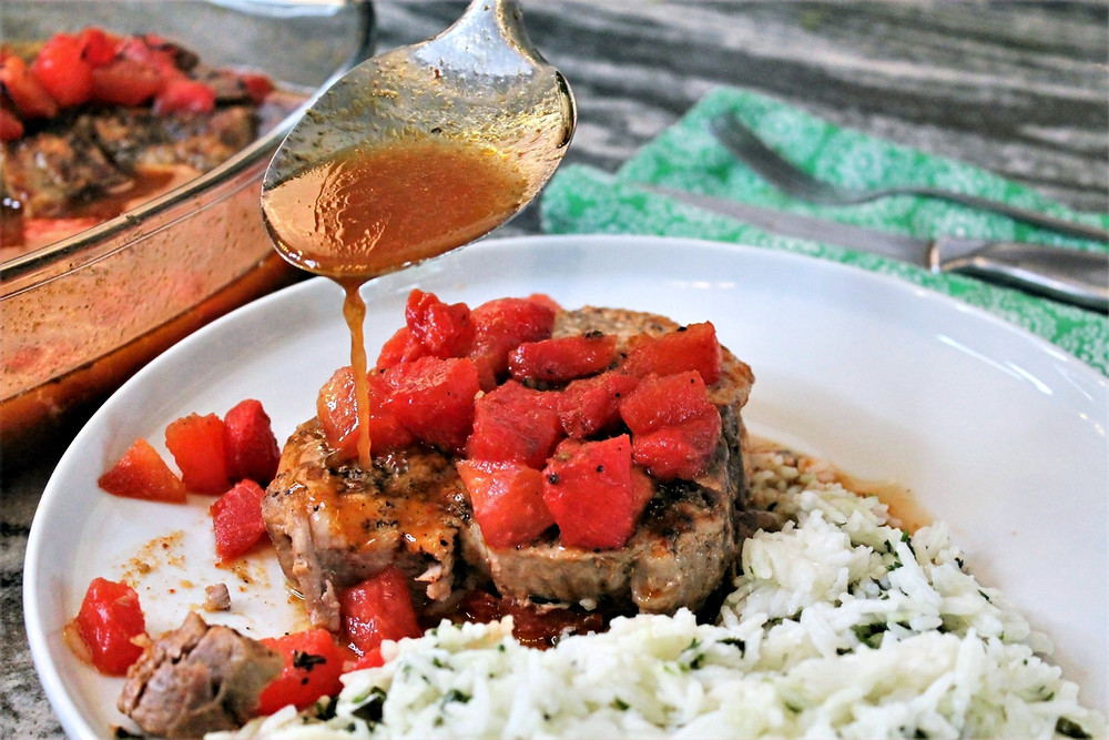 pouring juice over pork chop and pieces of watermelon. Herb rice on a plate