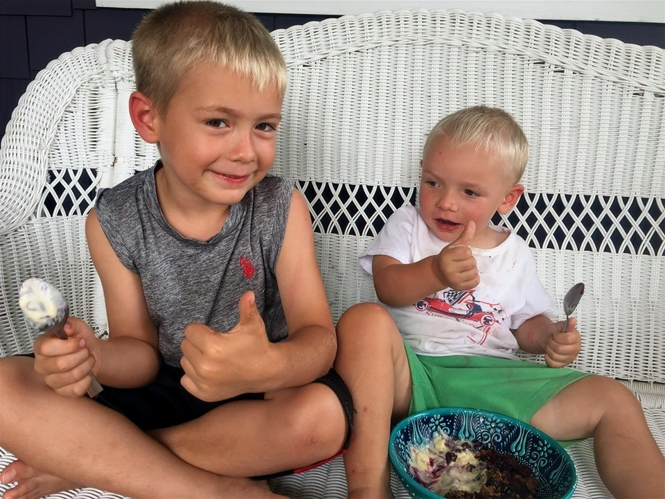 Two young boys enjoying homemade blueberry cobbler with homemade vanilla ice cream, giving the camera a thumbs up