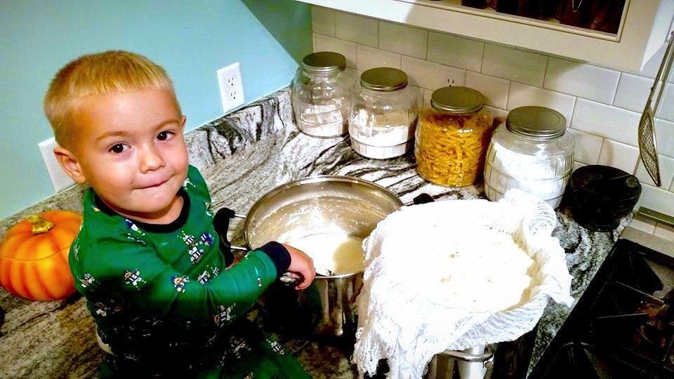 Thomas sitting on the counter and moving homemade cheese from the pot to the cheesecloth to drain