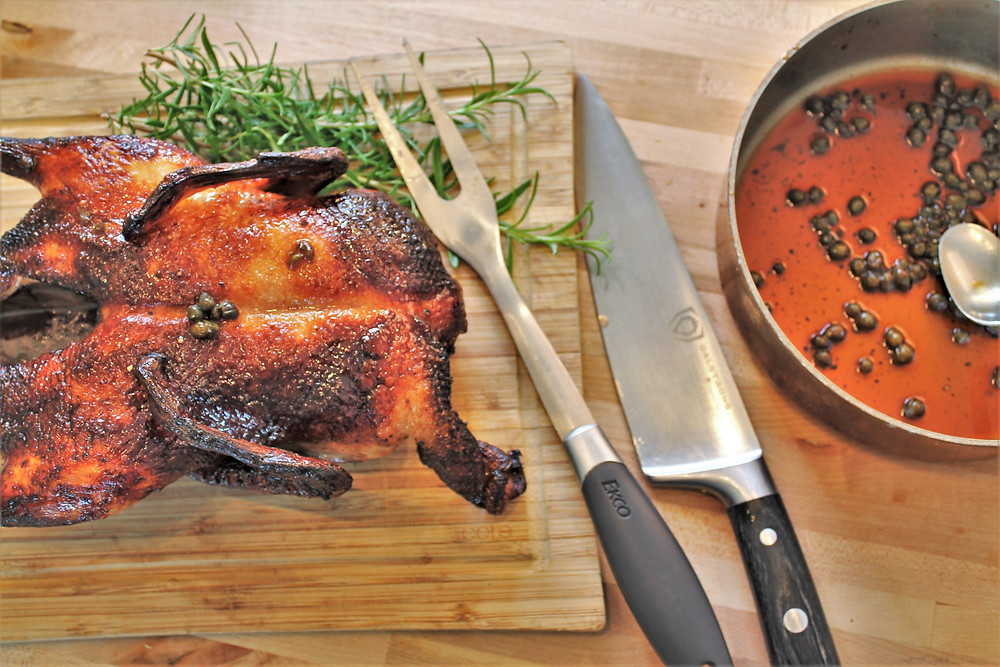 duck resing on a wooden board, knife, fork for curving meat, pan with glaze, spoon, and fresh rosemary