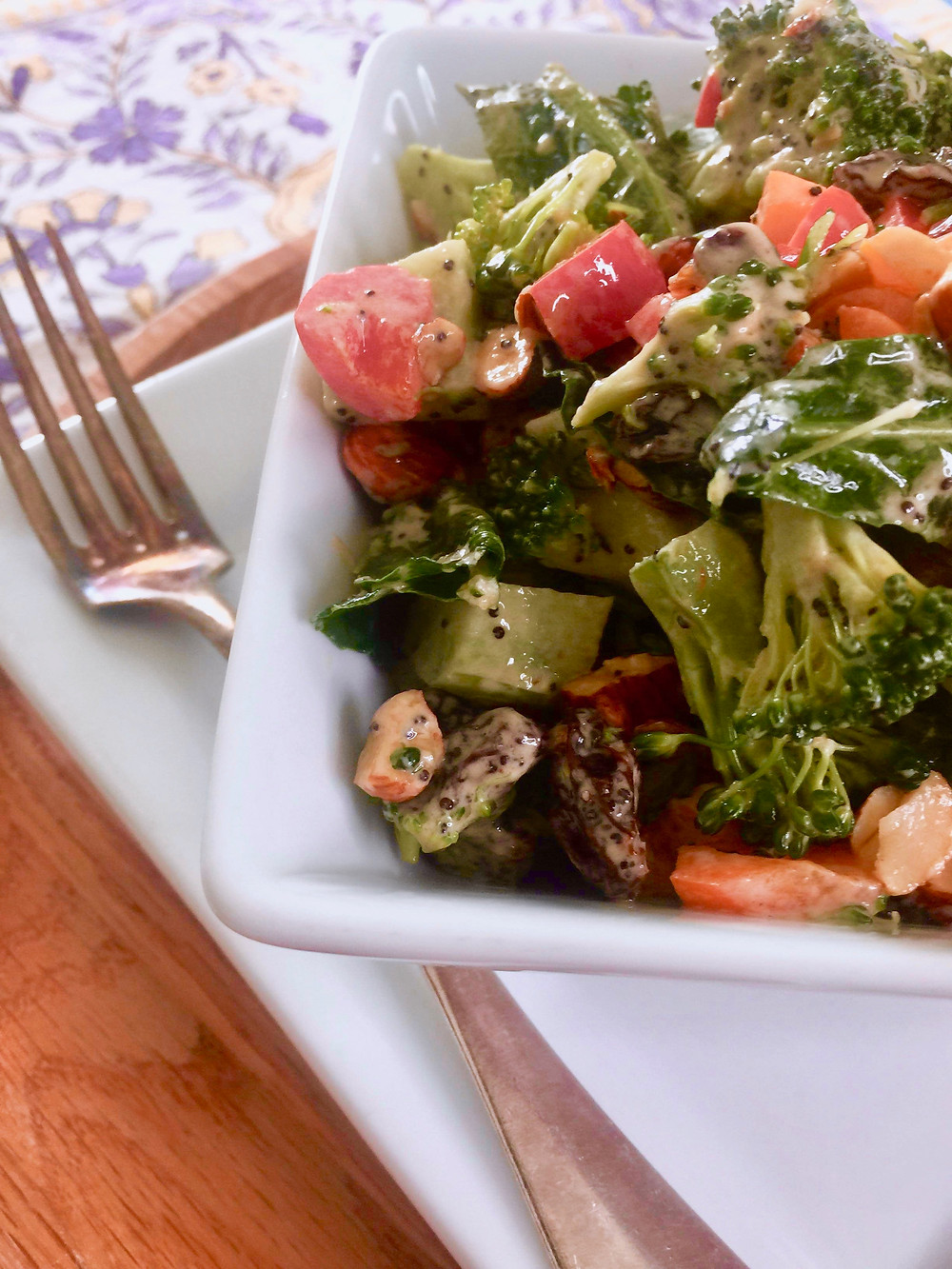 Broccoli salad with tahini poppy seed dressing in a bowl with a fork on the side