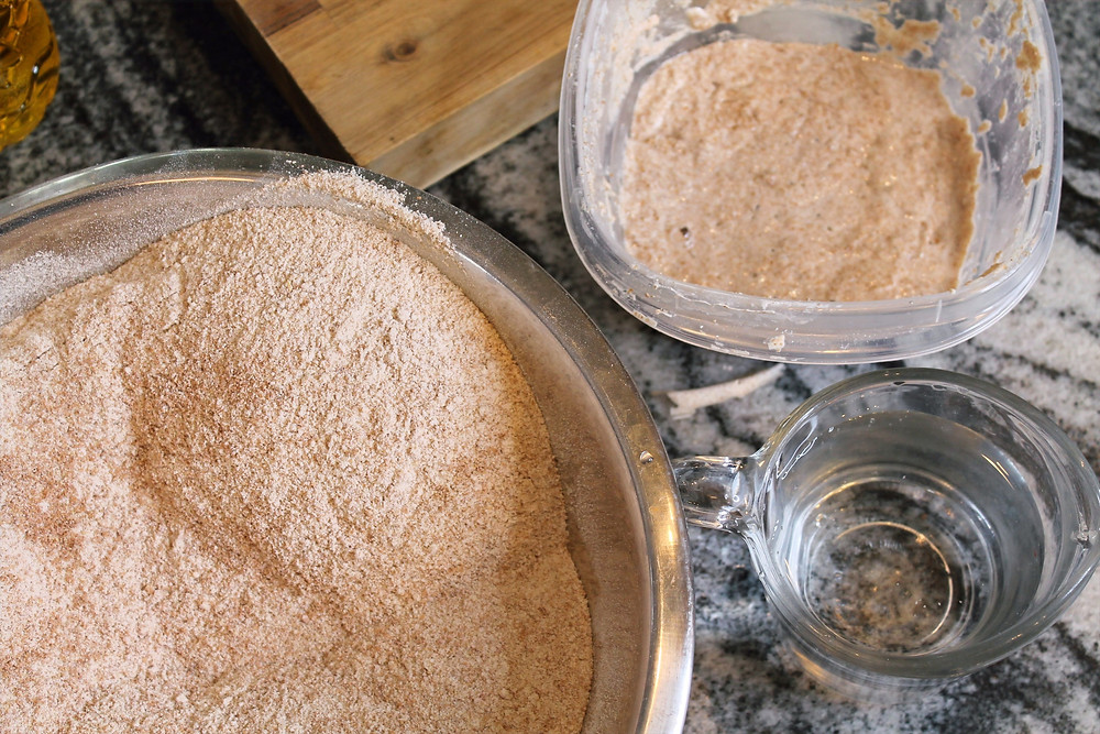 whole wheat flour in a bowl, water, starter