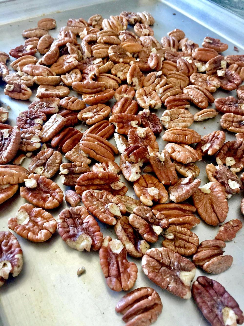 Pecans spread on a baking sheet, ready to roast