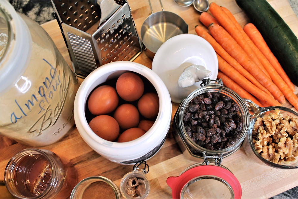 almond flour in a jar, eggs, honey, raisins, walnuts, carrots, zucchini