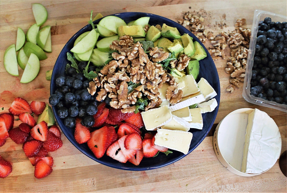 on a wooden board strawberries, apple slices, walnuts, blueberries, brie