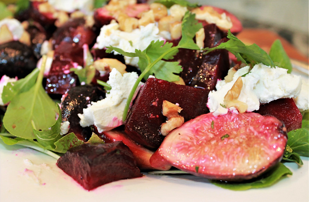 Close-up of fig-beet salad with spinach, goat cheese, walnuts, and cilantro