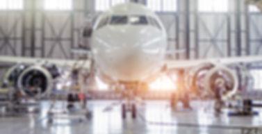 Airplane being serviced in a hangar.