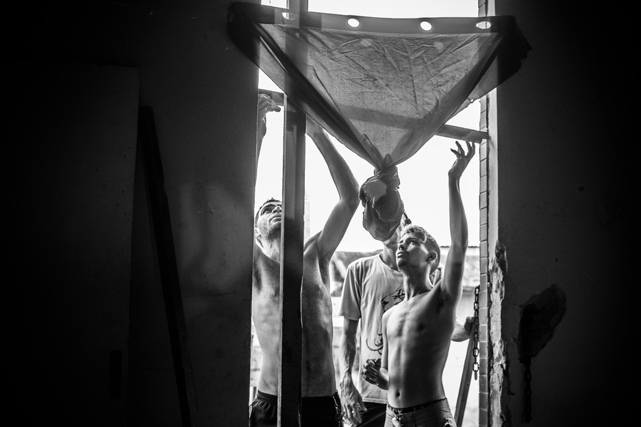 Three men building a door inside Vila da Manchete Occupation. Each occupant received a lot (5x5 meter), so they could build a new house and move with their families.