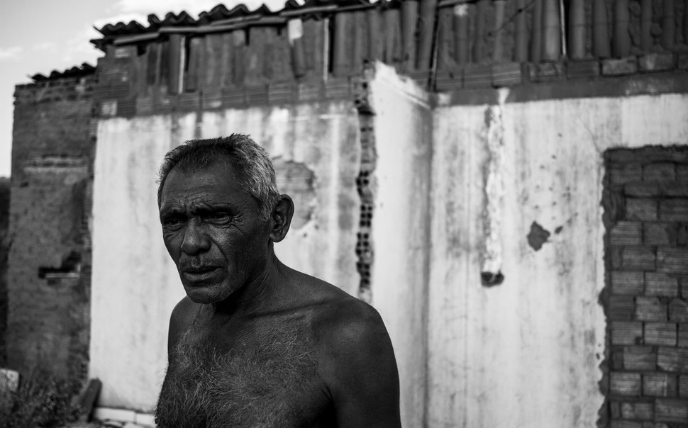 """Silzécio Bras, 59 stands in front of the ruins of his house. The construction of the canals also meant removing entire populations who lived along their trajectory. Silzécio was removed first from the house where he lived his entire life in the Sitio cipó district, between the states of Paraiba and Pernambuco. After building a new one two kilometers away from the first, he was informed that he had to move away and that half of the house was going to be demolished. A change of plans in the trajectory of the canal was putting his new house three meter's beyond the allowed space. """"For me, this work is only a disgrace. The explosions destroyed all my wells and I have no money for digging new ones. I lost two houses, and I'm still afraid of losing my third. I only see water when the tank-trucks bring it, and they only do that one time a month when we close the roads in protest."""""""