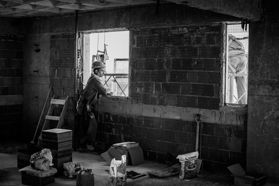 Even though the construction industry was hit hard by the crisis, the building is unstoppable. Yet many construction workers live in occupied spaces, squats, and, for them, living in one of the apartments they are building is a far-away dream.