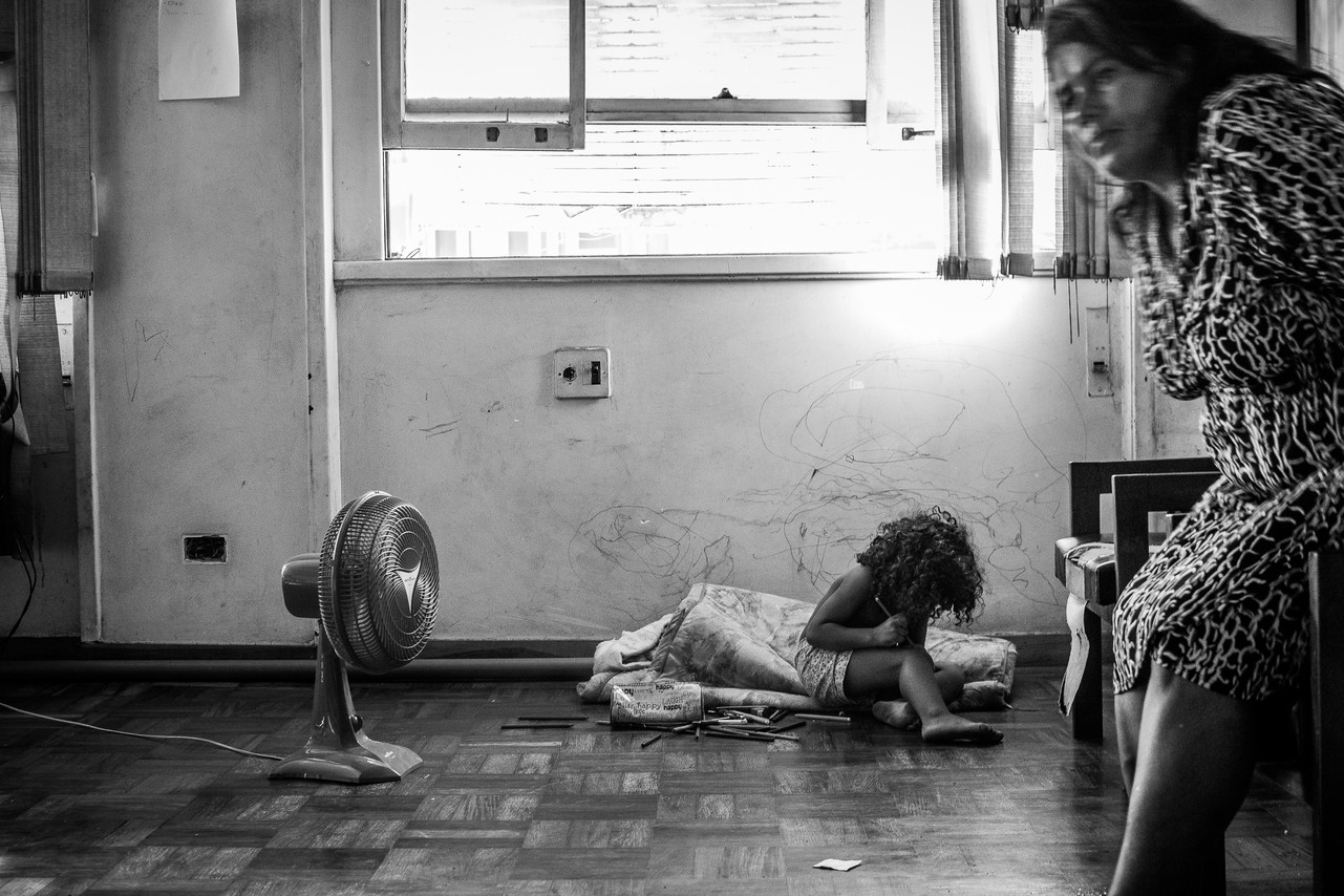 Eliane Santos Silva and her daughter waiting for dinner in the Marielle Franco Occupation. The occupation has a shared kitchen where three meals are prepared each day. The food comes mostly from donations and is available for everyone.