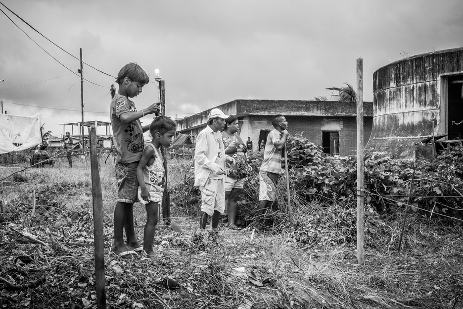 A group of occupants observes while men build a shack in the Vila da Manchete Occupation. Vila Da Manchete is being built below an old TV station. The occupants are workers from the community that surrounds the occupation, and every family gets a small lot to build their houses and to settle on.