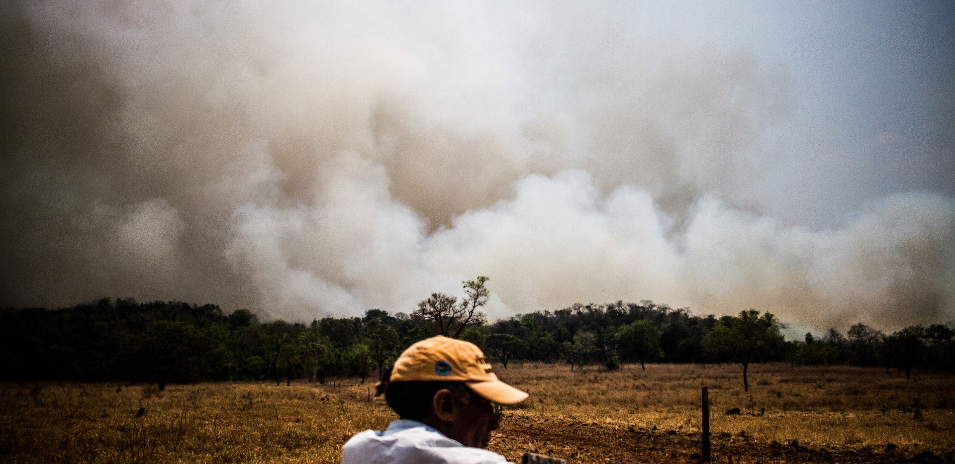 A Local Farmer in Nobres, State of Mato Grosso watches as a cloud of smoke rises from a fire on a farm.