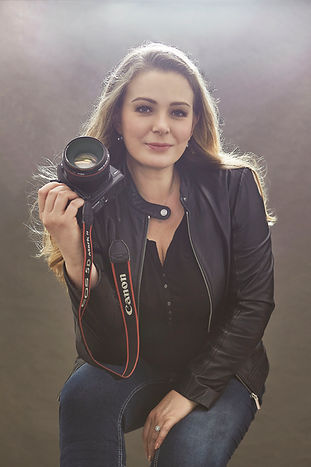 Aleksandra Walker photographer's portrait wearing jeens and black leather jacket and holding Canon camera