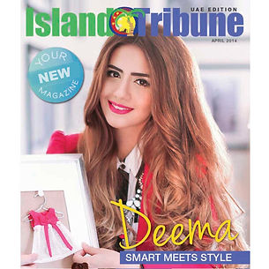 Deema AlAsadi's portrait on the Island Tribune magazine cover wearing bright pink jacket and black and white stripe shirt holding a little dress pinned in a picture frame