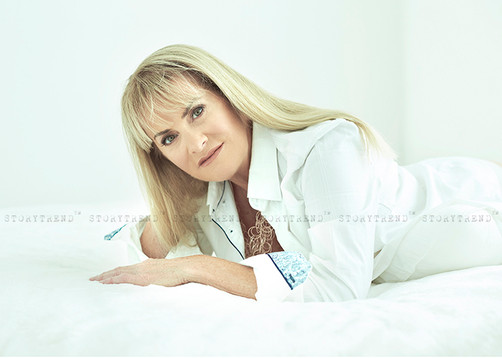 Mature blond woman wearing white man shirt laying on her tummy leaning on to her arm on a white bed in a white room, looking to the camera.