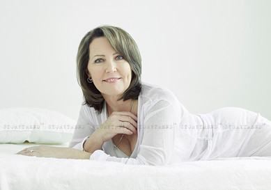 Mature light hair woman, wearing white dressing gown, laying on her tummy leaning on to her elbows on white bed in a white room, looking to the camera smiling.