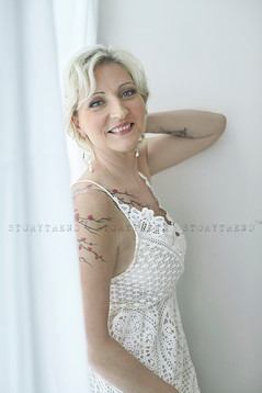 Mid age blond short hair woman with sakura tree tattoo on her shoulder and chest, wearing sleeveless lace white dress standing side way in a white room and leaning with her back to the window, smiling to the camera