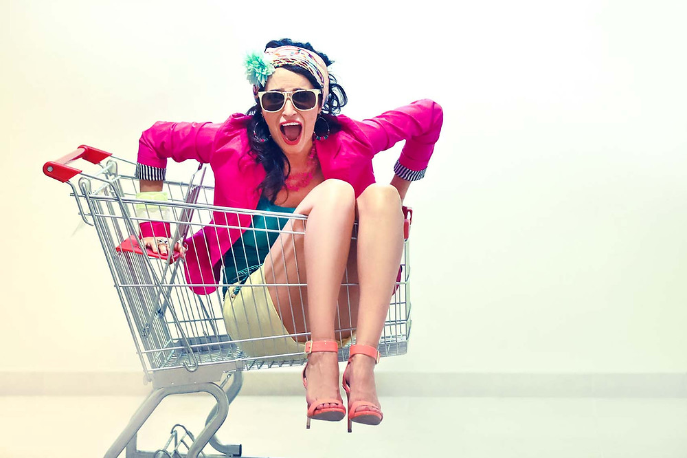 Colourfully dressed girl wearing hills and sunglasses sitting inside of a shopping cart. Fun photo of shouting girl.