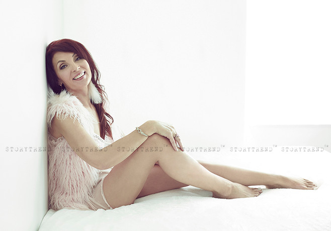 Mature long dark red hair woman wearing long light pink faux fur vest and feather earrings leaning to a white wall sitting on white bed sheets in white room smiling