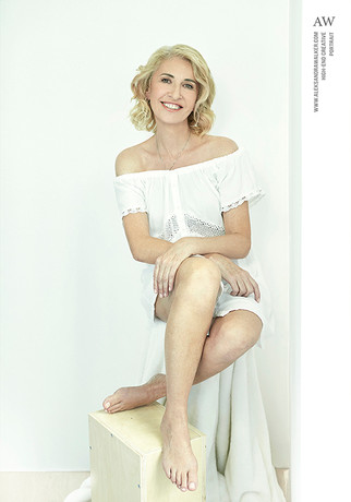 Before and after photos of a mature blond short hair woman, comparing her Polaroid before photo with no makeup and professional photo after her makeover, wearing short white dress, sitting on a posing chair with her legs on an apple box and smiling