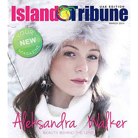 Aleksandra Walker's portrait on the Island Tribune Magazine cover wearing a white turtle neck, white fur hat and long black earrings on a winter forest background