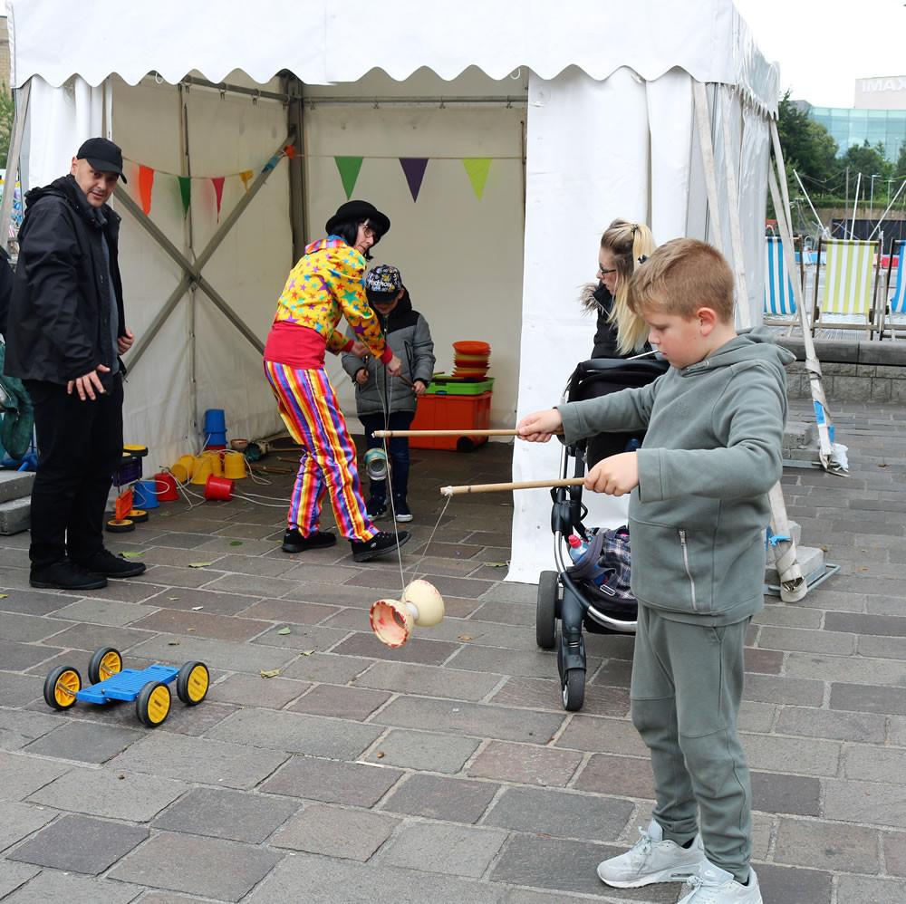 Boy learns Circus skills Bradford Festival 2019