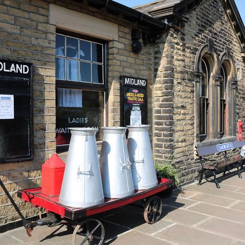 milk churns on cart, on platform at hist