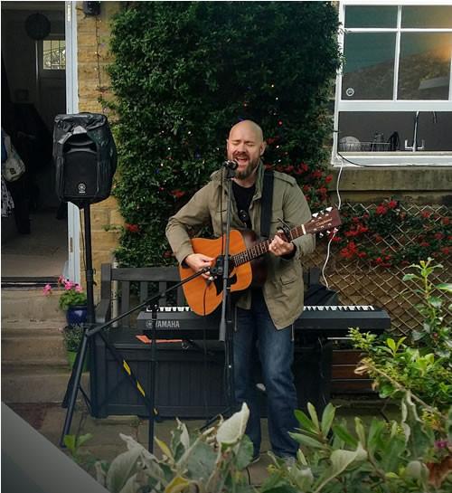 Man plays guitar Saltaire village