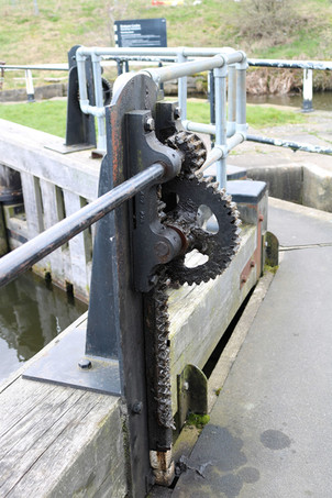 A canal lock gate sluice winding mechanism showing the wheels and cogs