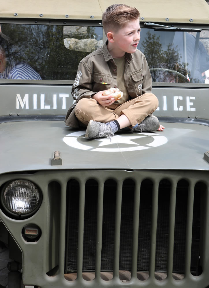 Boy sits on bonnet of military jeep vehicle