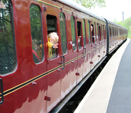 Child looks out of steam loco window coach Haworth