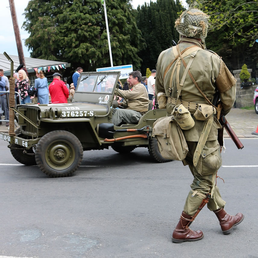 Soldier stop traffic to allow jeep to cross