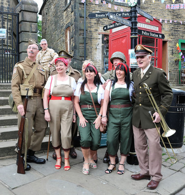 Group in period costumes on church steps Haworth 1940s