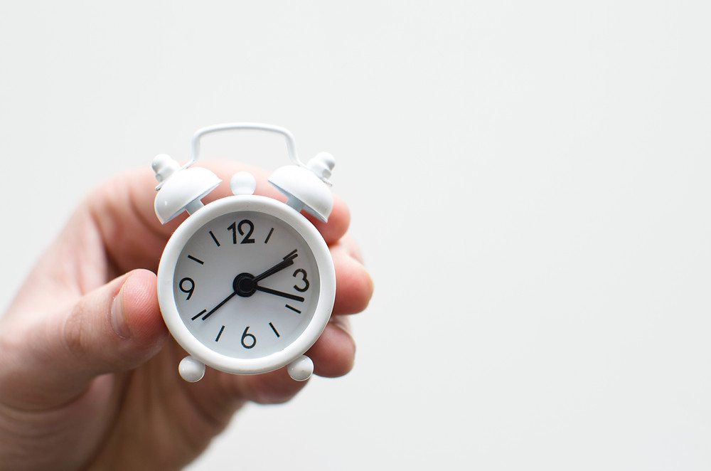 Hand holding a white clock