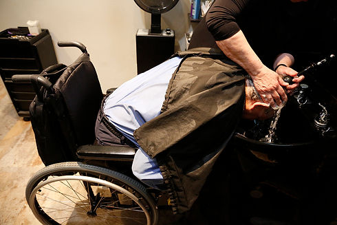 A man in his wheelchair getting his hair washed - Photo by Eichner Studios