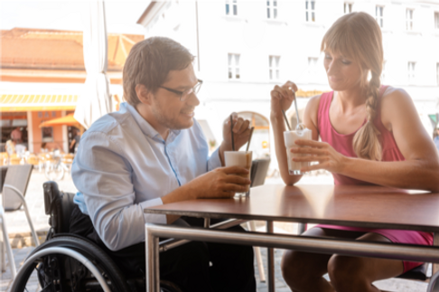 Woman and man in wheelchair drinking milkshakes in a restaurant
