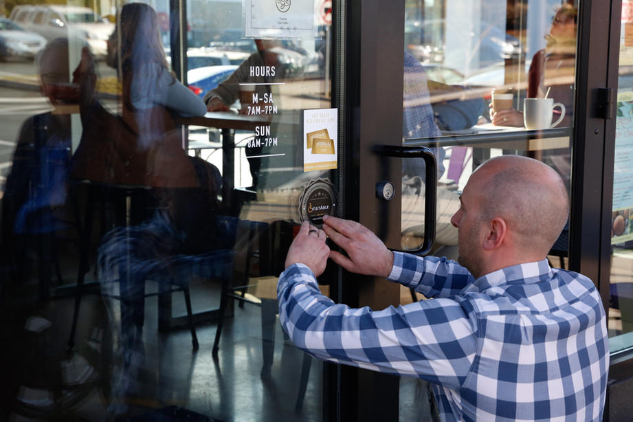 The Director of Operations of Grit Coffee is applying the certification sticker to his store. - Photo by Eichner Studios