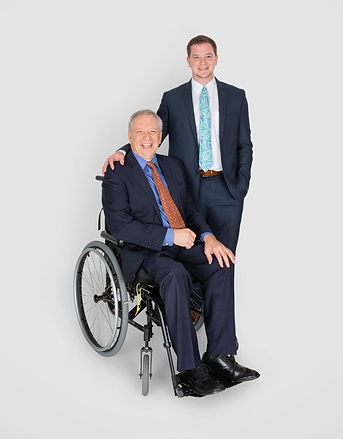 VisitAble's founder with his father, who uses a wheelchair. Both men are smiling and dressed in suits and ties. VisitAble founder has his right hand on his father's right shoulder. - Photo by Eichner Studios