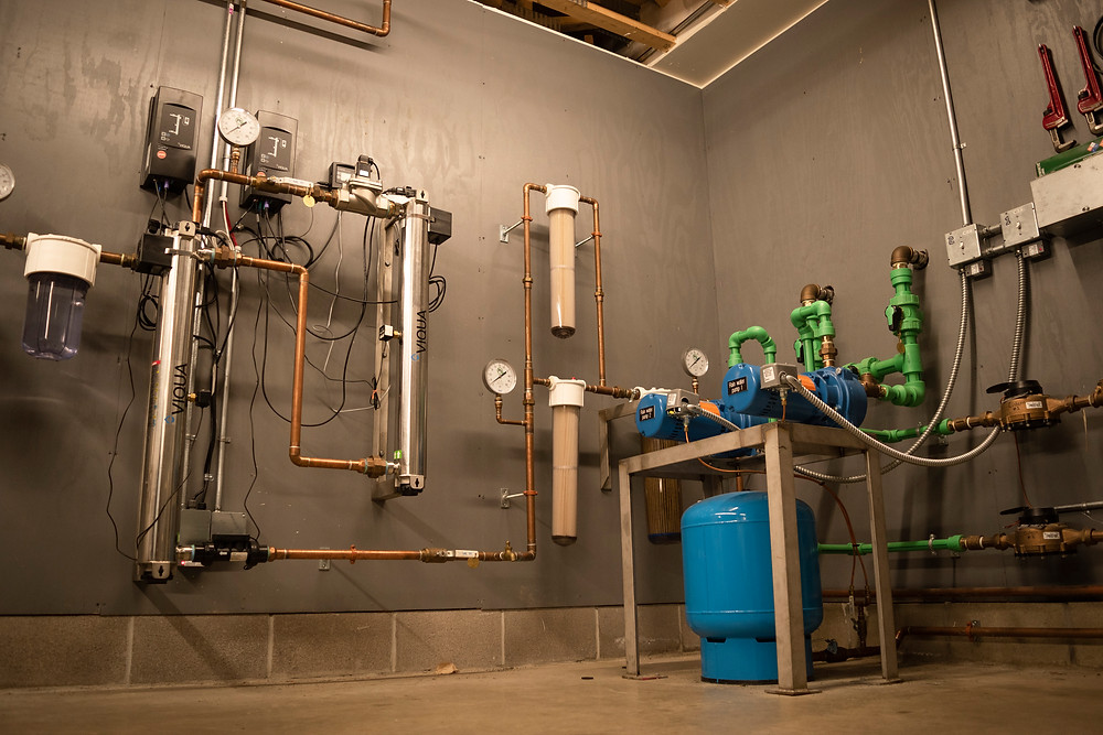 The R. W. Kern Center's rainwater filtration room is pictured with pipes covering two walls.