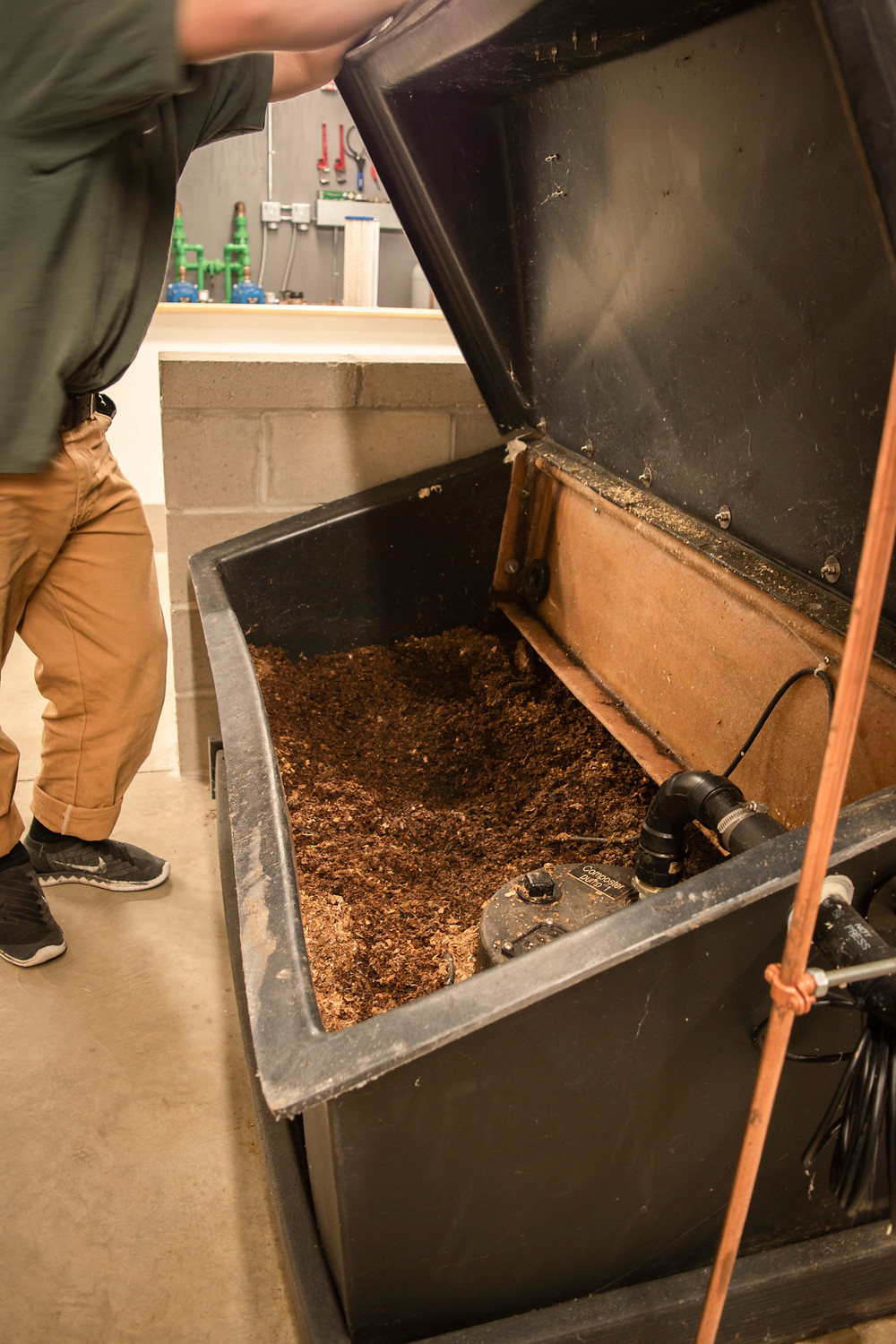 Oliver opens the waste bin which has organic mulch recycled from the composting toilets.  At this stage it is just nutrients remaining from the waste.