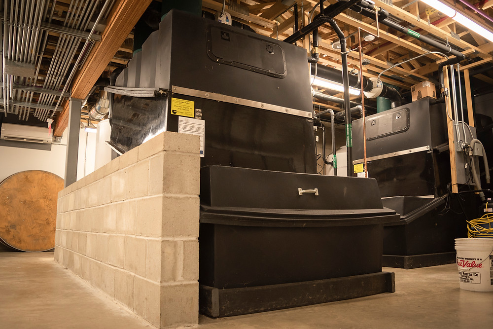 The R. W. Kern Center's waste collection bins are pictured, one center and one center right which hold the final step for waste filtration from the building. Both are black and occupy space from the floor to the ceiling.